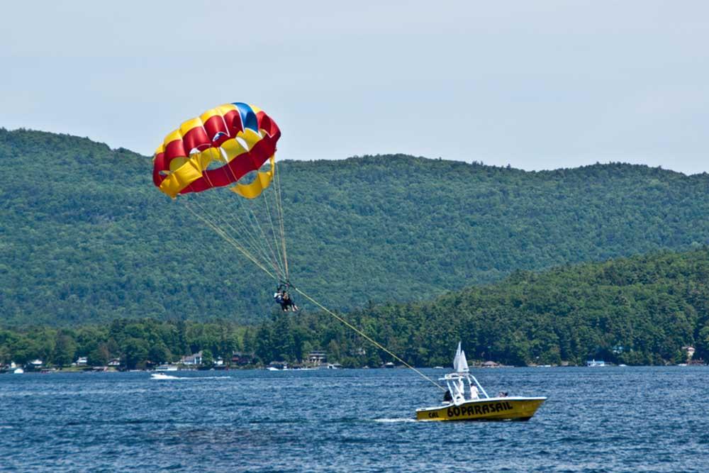 People parasailing behind boat on lake