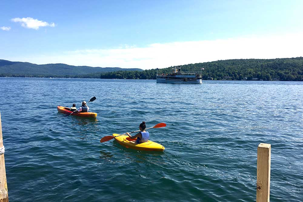 family kayaking on lake with Cruise boat in background