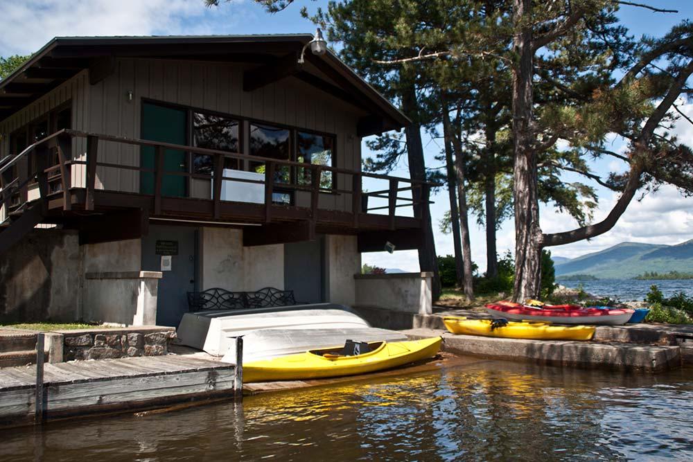 Kayaks docked by lakeside boathouse and villa